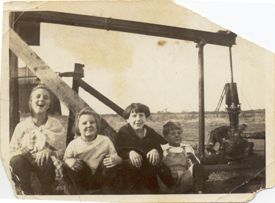 My grandfather, in overalls, with his siblings, in front of one of the family's pumpjacks near Wilson, Oklahoma around 1920. Looks like a good day on the prairie!